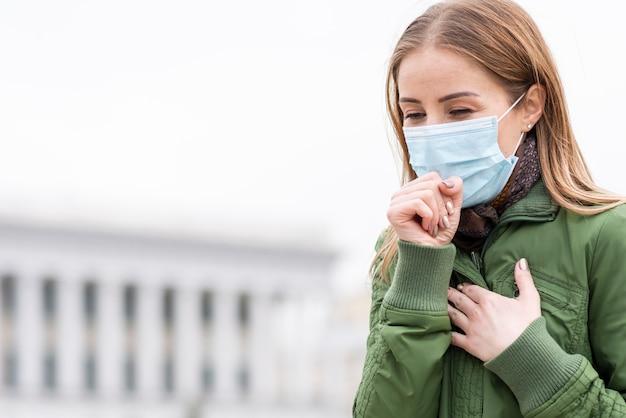 Mujer tosiendo en el espacio público