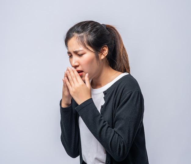 Una mujer tosiendo y tapándose la boca con la mano.