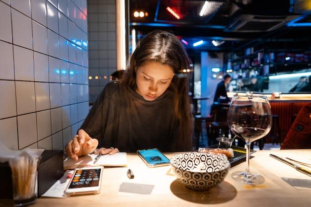 Mujer trabaja en un café en la noche