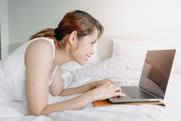 La mujer trabaja con la computadora portátil en el concepto de trabajo de la cama del hotel