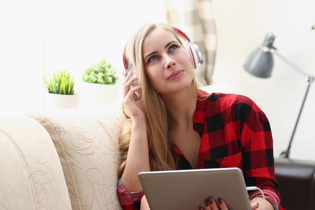 Mujer trabaja en la computadora portátil escucha auriculares de música