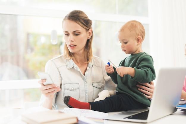 Una mujer trabaja durante la licencia de maternidad en casa.