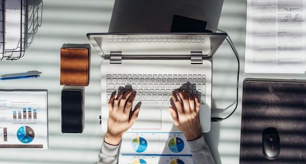 La mujer trabaja con el portátil en la mesa de trabajo.