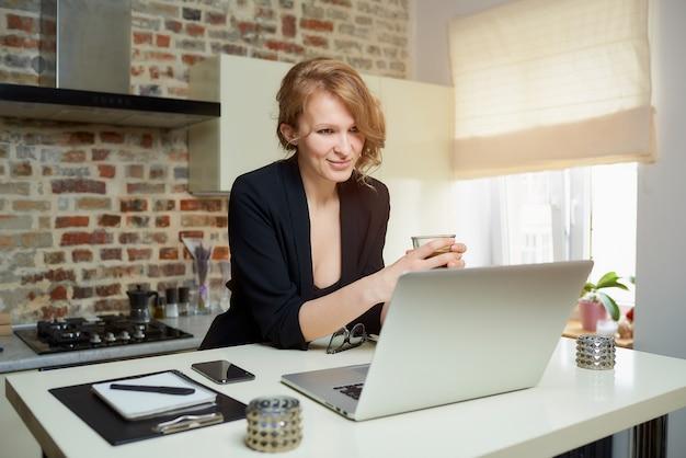 Una mujer trabaja remotamente en una computadora portátil en una cocina. una niña feliz sostiene una taza de café escuchando el informe de un colega en una video conferencia en casa.