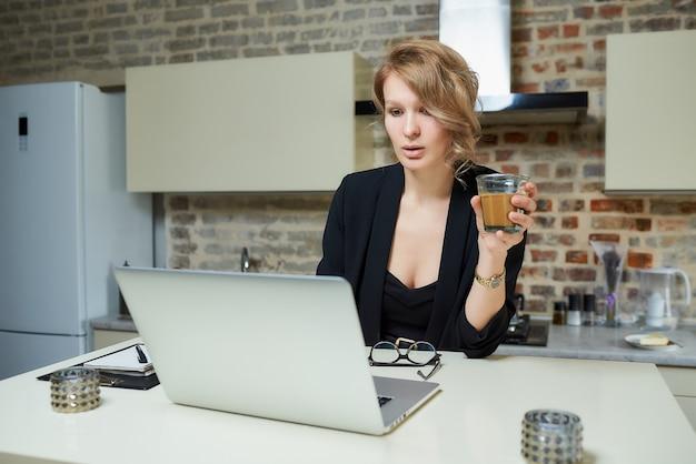 Una mujer trabaja remotamente en una computadora portátil en su cocina. una señora sostiene un vaso de café preparándose para una conferencia en una videollamada.