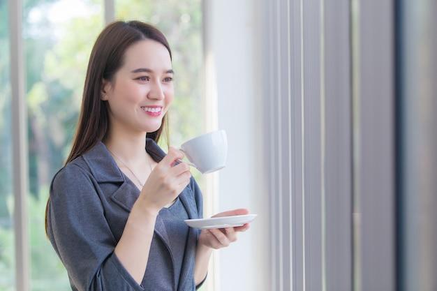 Mujer trabajadora asiática está mirando por la ventana para pensar algo mientras sostiene la taza de café en la mano.