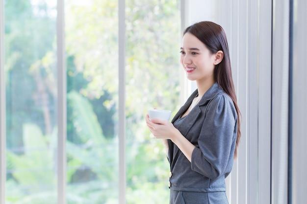 Mujer trabajadora asiática viste soportes de vestido gris y sostiene una taza de café en sus manos por la mañana