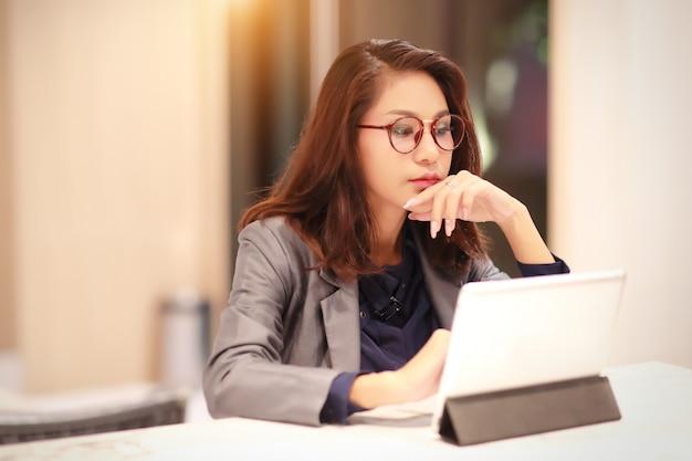 Mujer trabajadora y encantadora con gafas usando tableta (concepto de trabajo desde casa)