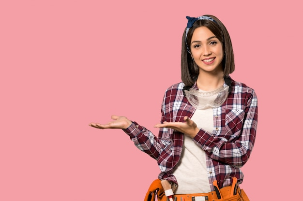 Mujer trabajadora joven que presenta una idea mientras mira sonriente hacia la pared rosada aislada