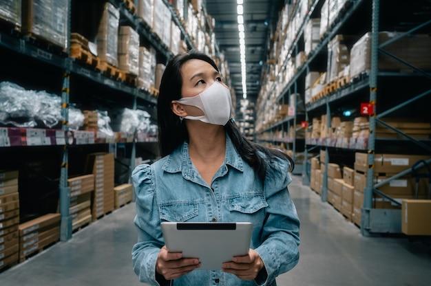 Mujer trabajadora de negocios asiáticos usan máscara con tableta digital que controla el stock de productos en el almacén