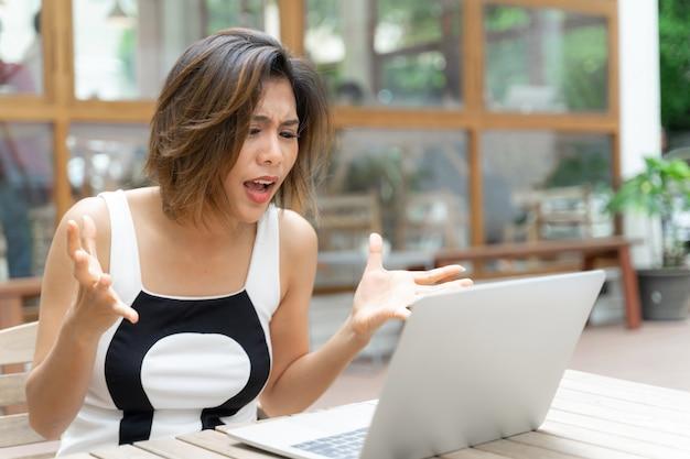 Mujer trabajadora que se siente molesta con la computadora portátil