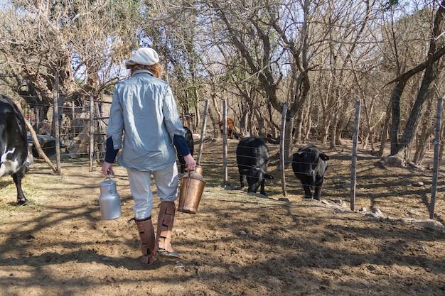Mujer trabajadora rural caminando en la campiña argentina con latas de leche recién ordeñada