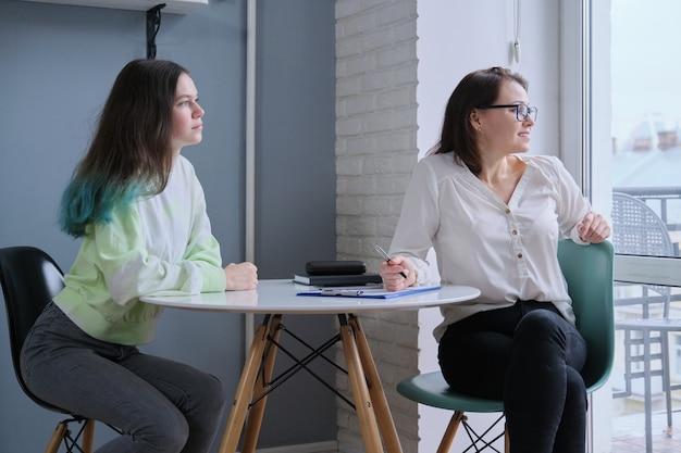 Mujer trabajadora social hablando con una adolescente