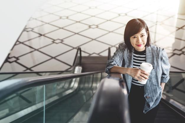 Mujer trabajadora con taza de café en escalator