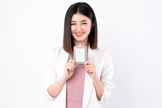 Mujer trabajadora con traje de negocios mostrando su tarjeta de identificación