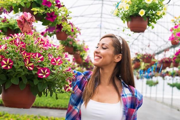 Mujer trabajadora de vivero de floristería sosteniendo flores en macetas y sonriendo en el centro de jardinería