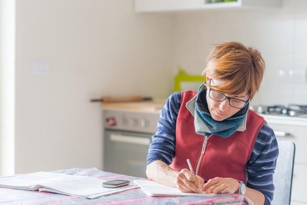 Mujer trabajando en casa, leyendo y escribiendo documentos