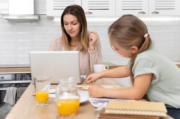 Mujer trabajando en casa con niña