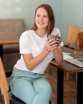 Mujer trabajando desde casa durante la pandemia mientras toma café