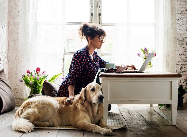 Mujer trabajando en casa con su perro.