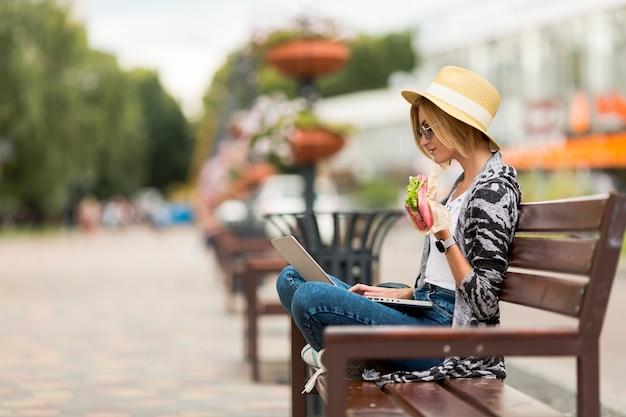 Mujer trabajando y comiendo en un banco