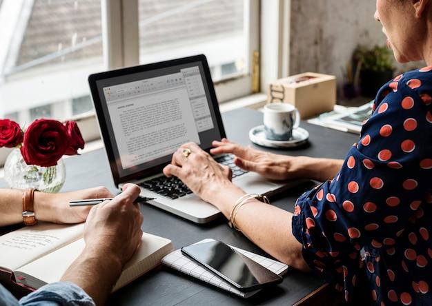 Mujer trabajando en computadora portátil escribiendo información de ensayo