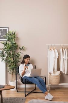 Mujer trabajando en la computadora portátil y sosteniendo una tarjeta en la sala de estar