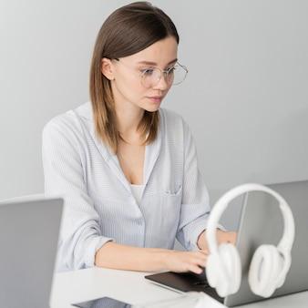 Mujer trabajando en una computadora portátil con sus auriculares colgando