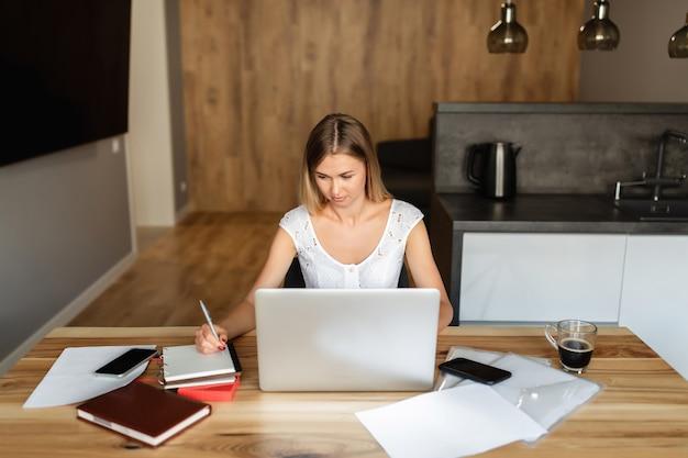 Mujer trabajando y estudiando en la computadora portátil en la oficina en casa