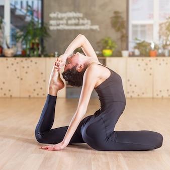 Mujer trabajando en el estudio haciendo ejercicios de estiramiento sentado en una postura de yoga con las piernas de una paloma real
