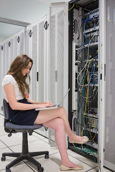 Mujer trabajando en laptop con servidores