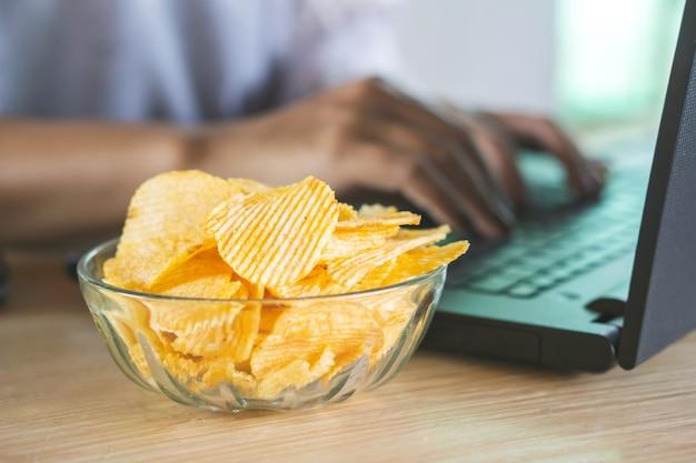Mujer trabajando y papas fritas en el escritorio de oficina