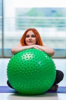 Mujer trabajando con pelota suiza en el estudio