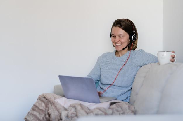 Mujer trabajando remotamente en casa con laptop y auriculares