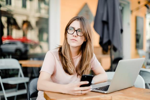 Mujer trabajando remotamente con laptop y teléfono en cafe