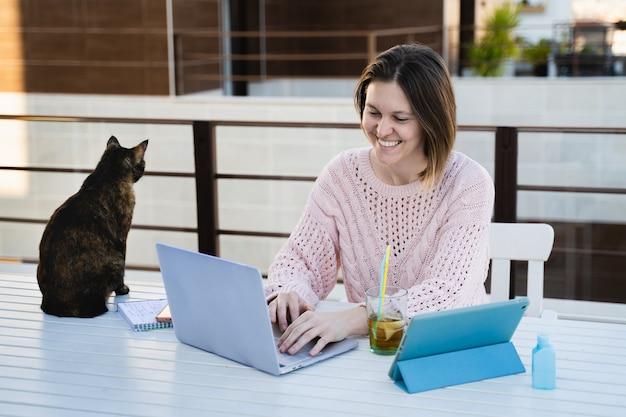 Mujer trabajando remotamente en la terraza de su casa con su mascota