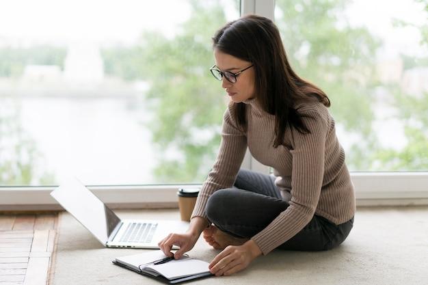 Mujer trabajando en su computadora portátil en el piso