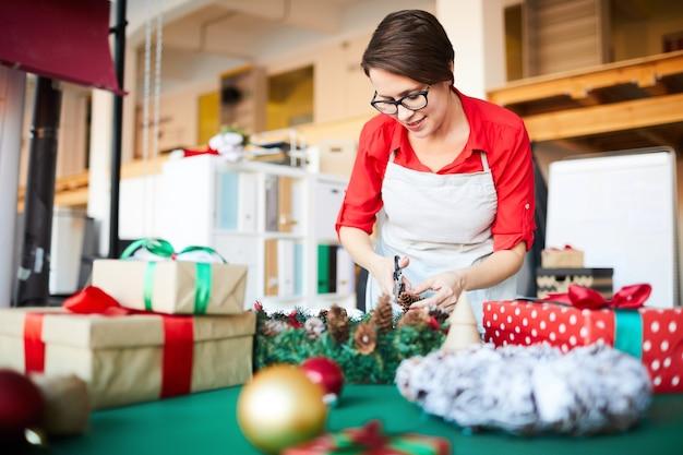 Mujer en el trabajo, haciendo una corona de navidad y envolviendo regalos.
