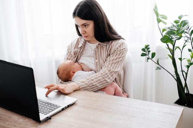 Mujer de trabajo que amamanta con bebé cerca de la computadora portátil