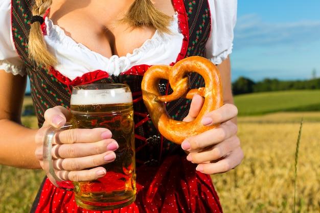 Mujer con tracht, cerveza y pretzel en baviera.
