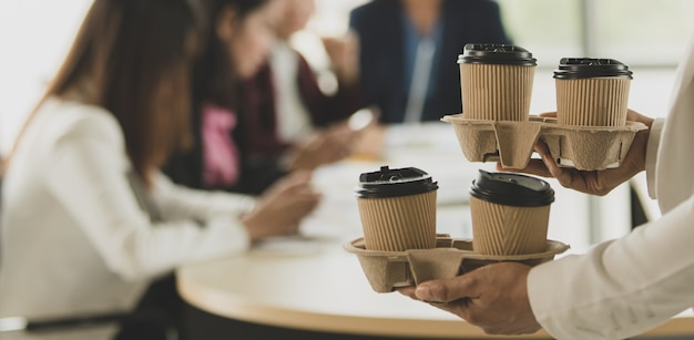 La mujer trae vasos de papel para llevar de café a la oficina durante el grupo de empleados, colegas sentados y trabajando en la mesa de trabajo y luego saludan y son felices con amabilidad. concepto de trabajo en equipo.