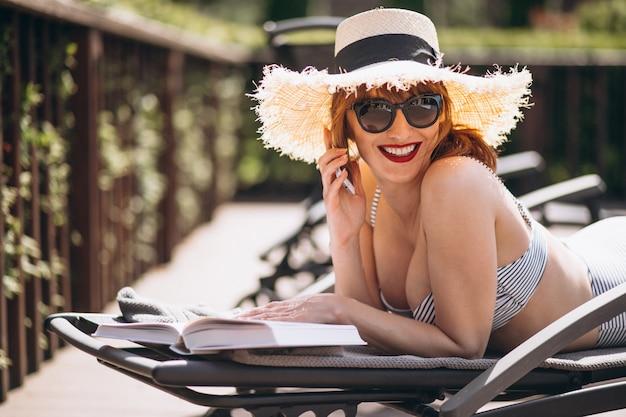 Mujer en traje de baño acostada en una cama y leyendo un libro