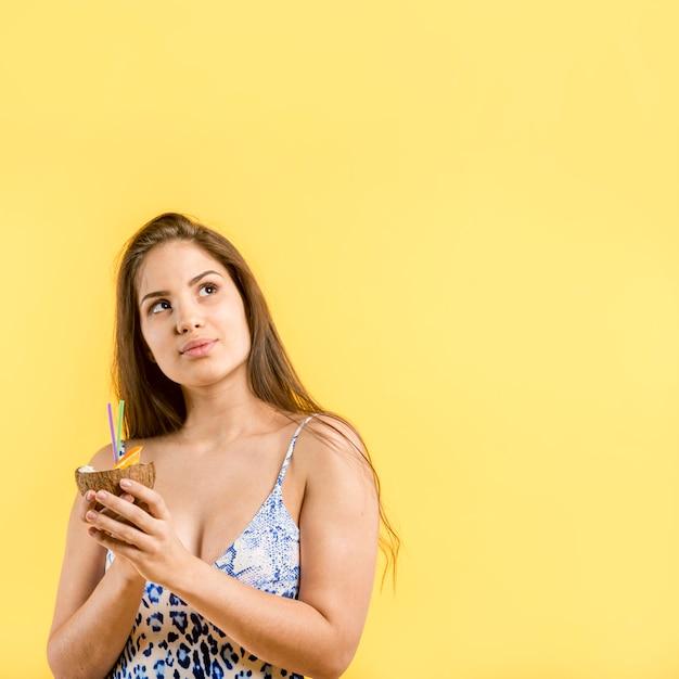 Mujer en traje de baño azul de pie y sosteniendo bebida de coco en las manos