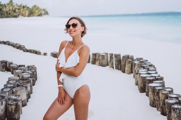 Mujer en traje de baño blanco junto al mar