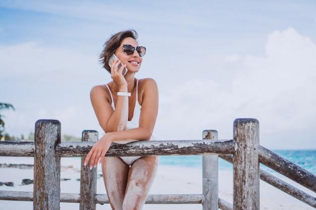 Mujer en traje de baño blanco junto al océano con teléfono