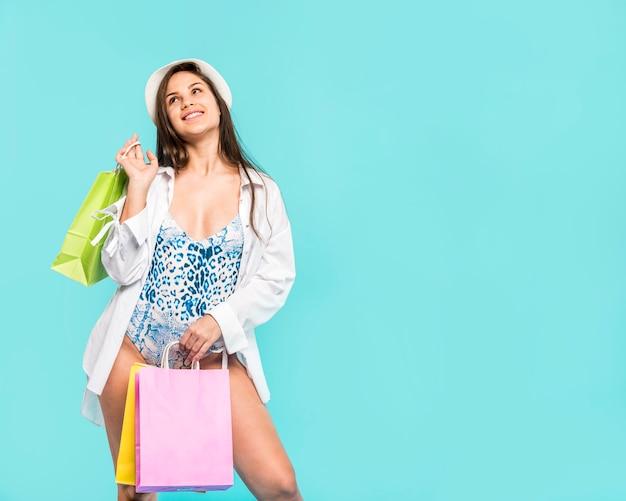 Mujer en traje de baño con bolsas de la compra.