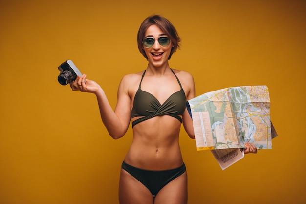 Mujer en traje de baño con cámara y mapa de viaje aislado