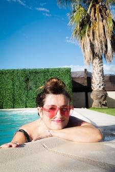 Mujer en traje de baño y gafas de sol relajándose en la piscina