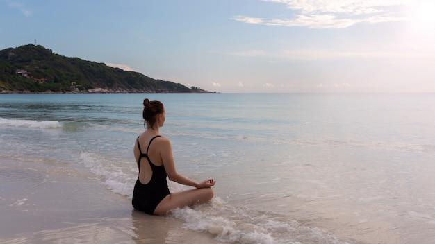 Mujer en traje de baño haciendo yoga en la playa