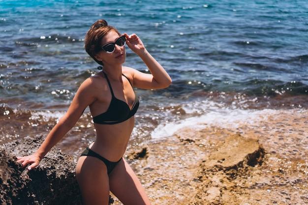 Mujer en traje de baño junto al mar
